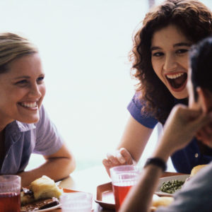 Friends laughing around table