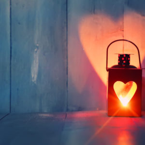 Lantern glowing red with a heart shaped cut out