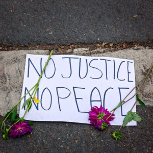 No Justice, No Peace sign lays on pavement with flowers around it