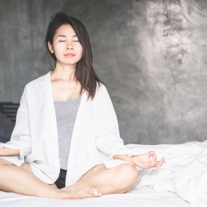 Beautiful Asian woman taking deep breaths with prenatal yoga