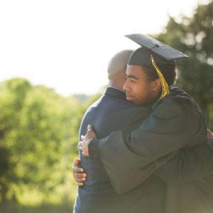 father hugging graduate