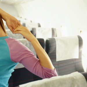Woman in airplane with hands behind head, eyes closed
