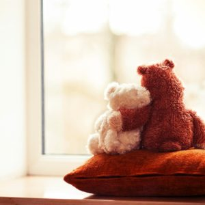 Two teddy bears embracing on pillow