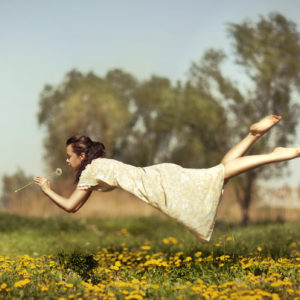 A woman floats above a field