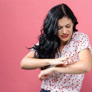 woman scratching arm, suffering from eczema