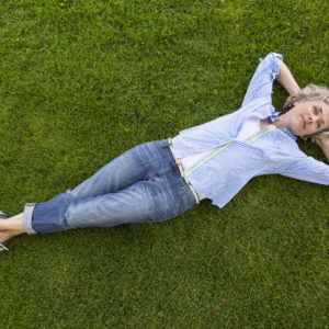 woman relaxing on green grass lawn
