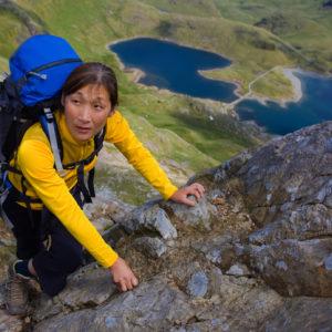 Woman climbing rocky mountainside