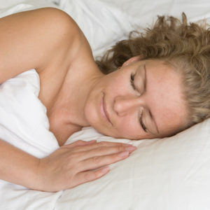 A woman sleeping on a comfortable bed.
