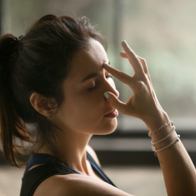Woman doing yoga using alternate nostril breath technique