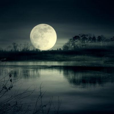A moon rising above a lake.