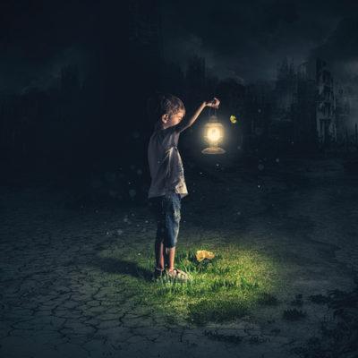 a boy navigates the darkness with a lantern