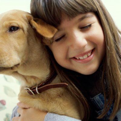 Young girl giving puppy a spiritual hug