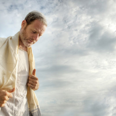 Jewish man engaged in morning prayers.