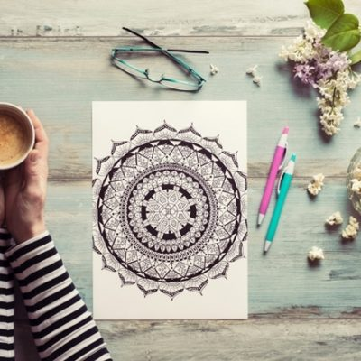 Woman with coffee and coloring boook