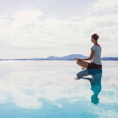 Calm scene of woman meditating on water