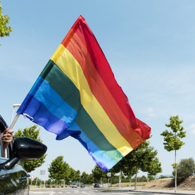 Rainbow flag waving out of car