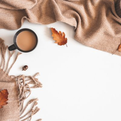 An autumn composition: cup of coffee, plaid, autumn leaves to show the yin of fall