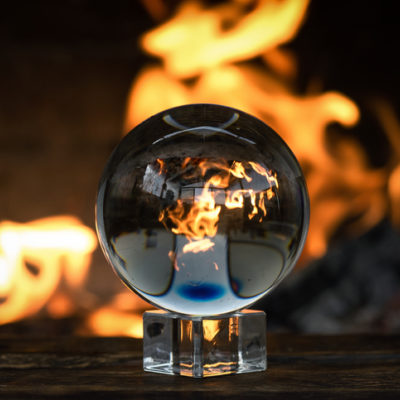 Crystal ball on a magic table on a burning fire flame background.