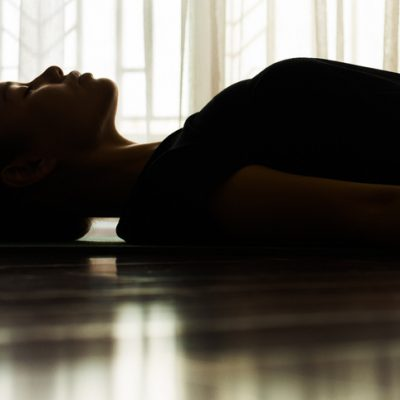 woman lying on back for guided sleep meditation for healing from injury or illness