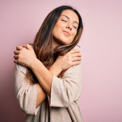 Woman hugging herself and smiling as a self-love practice