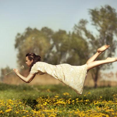 A woman floats above a field