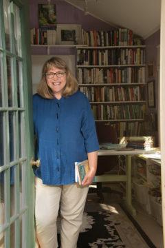 Diana Butler Bass standing next to bookshelf