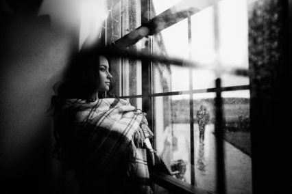 Young Woman Looking Through Window Hugging Herself Alone