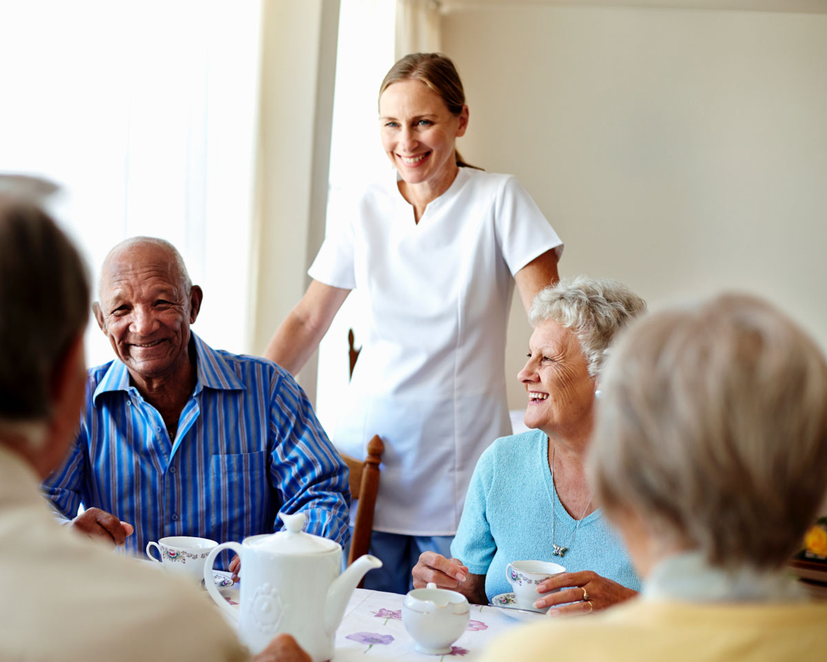 a senior living staff member checks in on a group of seniors having tea