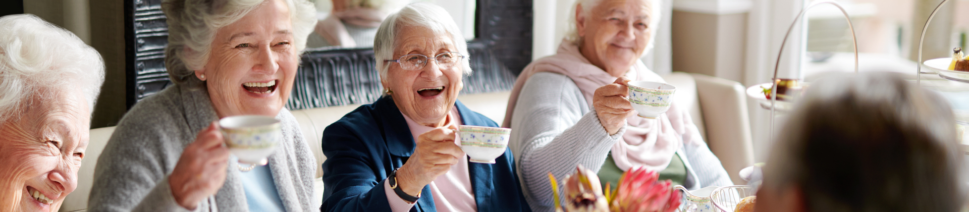 A group of seniors toast with fine china and tea