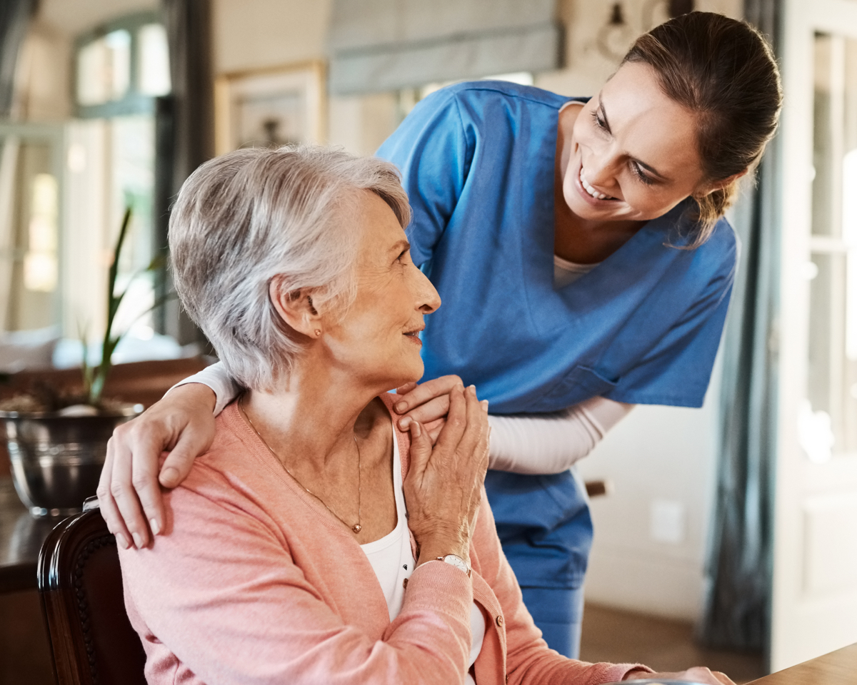 A health care professional places her hands on a seated senior