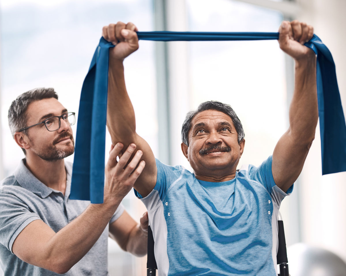 A rehabilitation services specialist helps a man strengthen muscles