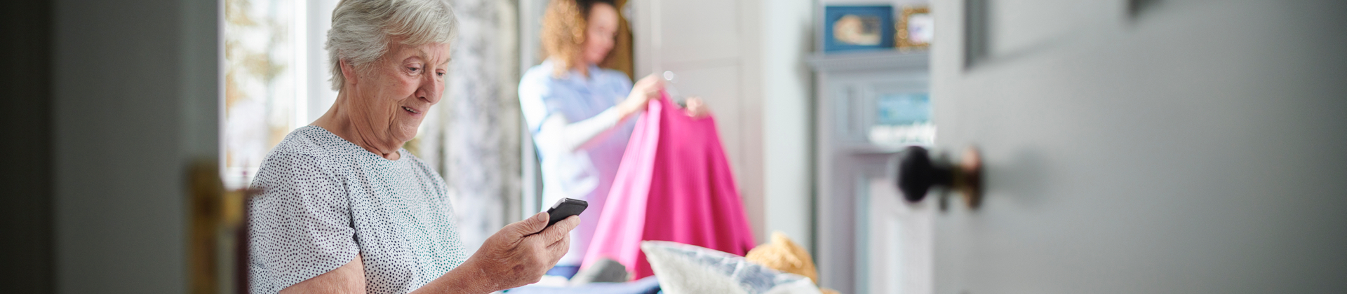 A senior woman looks at her cellphone while in the background someone is helping her hang up clothes