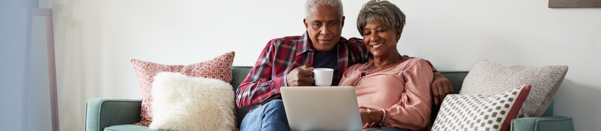 A senior couple sit on the couch and look at a laptop