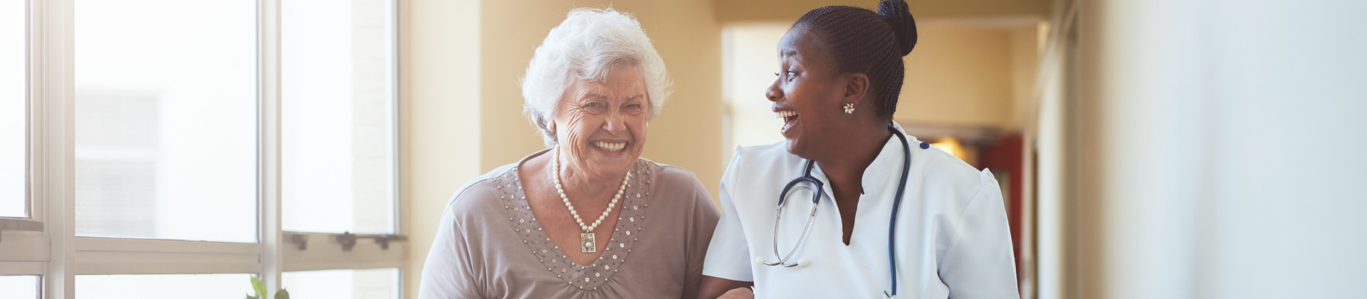 A health care professional laughs with the resident while walking a senior woman down a hallway