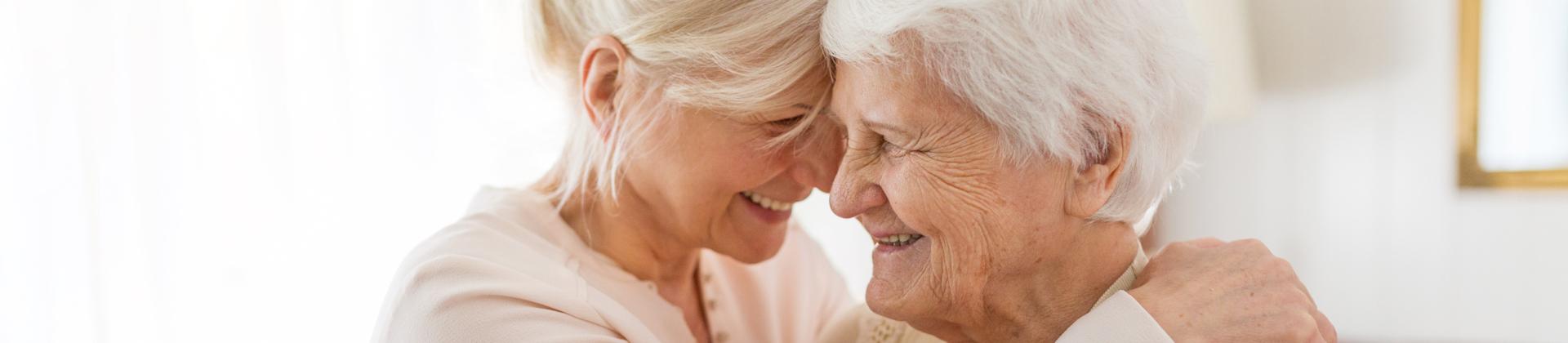 A woman hugs her elderly mother