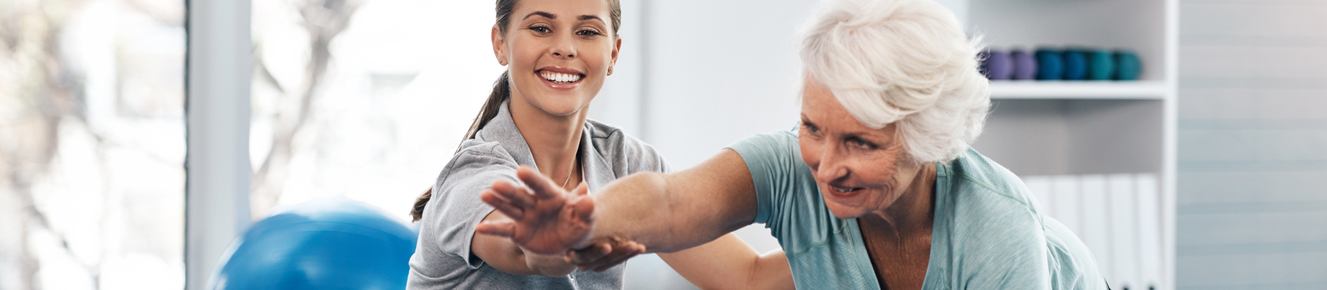 A physical therapist helps a senior woman do yoga stretches