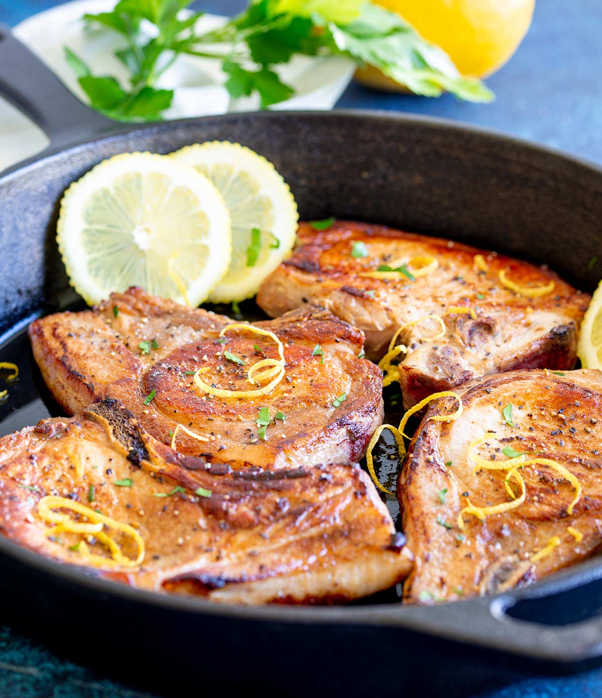 4 cooked chops in a pan with lemon and parsley in the background