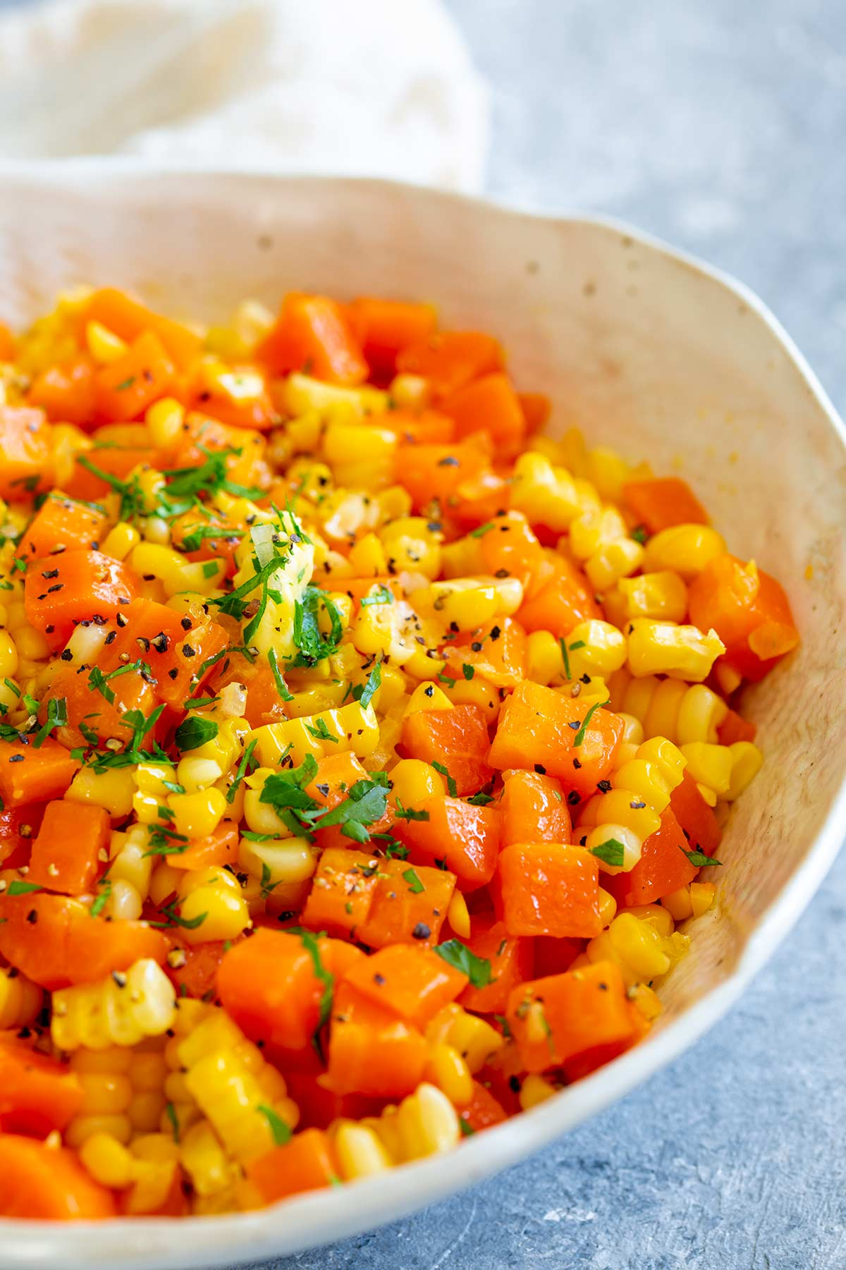 a whit bowl of chopped and buttered cooked carrots and corn