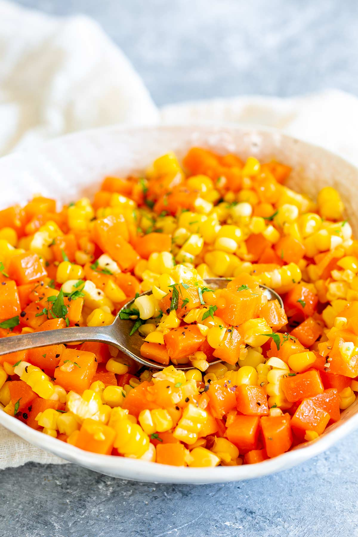 a spoon scooping up carrots and corn from a white bowl