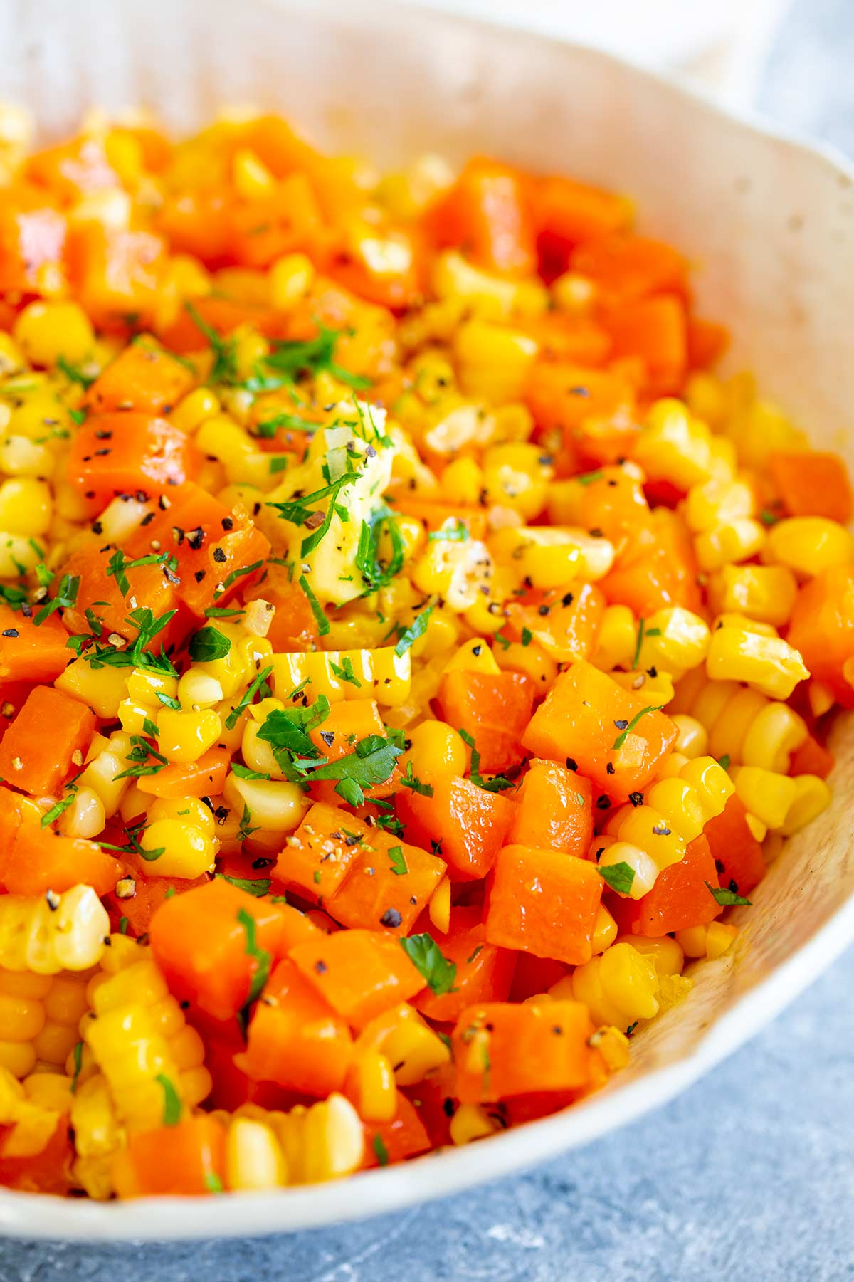 chopped carrots and corn garnished with parsley and pepper