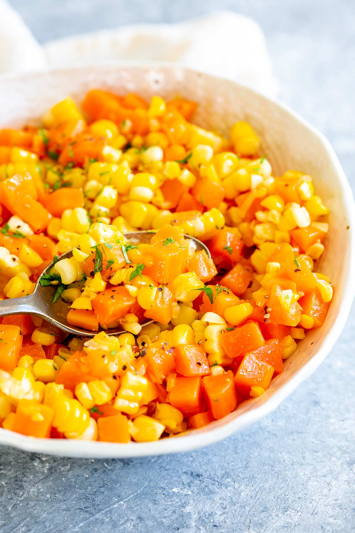 a whit bowl of carrots and corn on a grey table