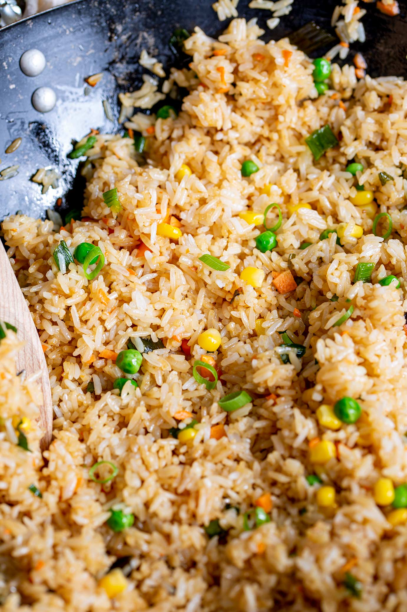 a wok of fried rice with peas, corn, carrots and green onion