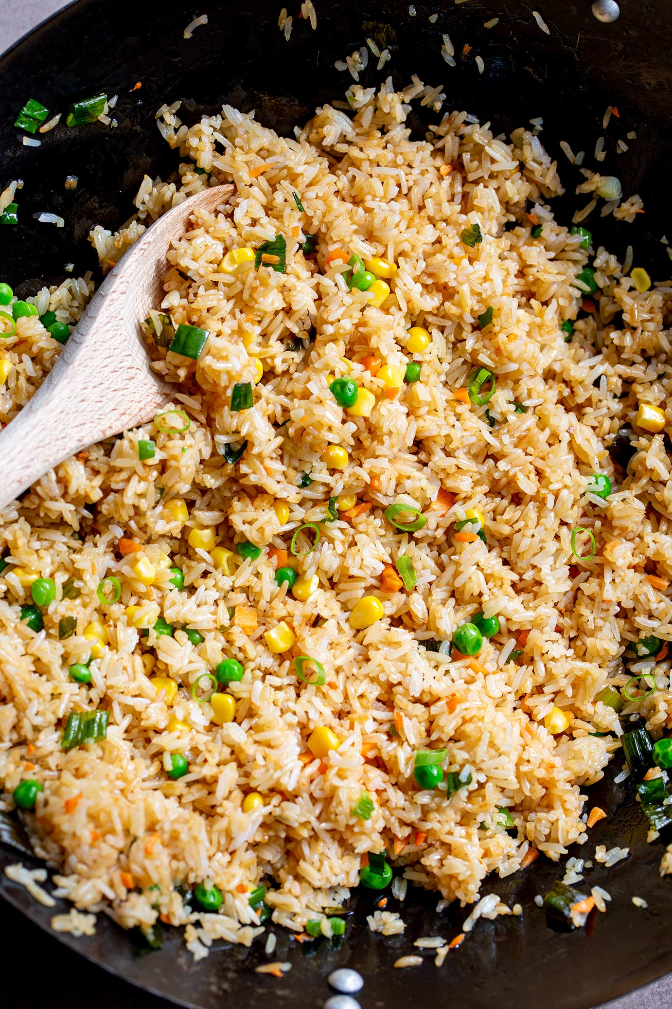 a wooden spoon in a wok full of fried rice