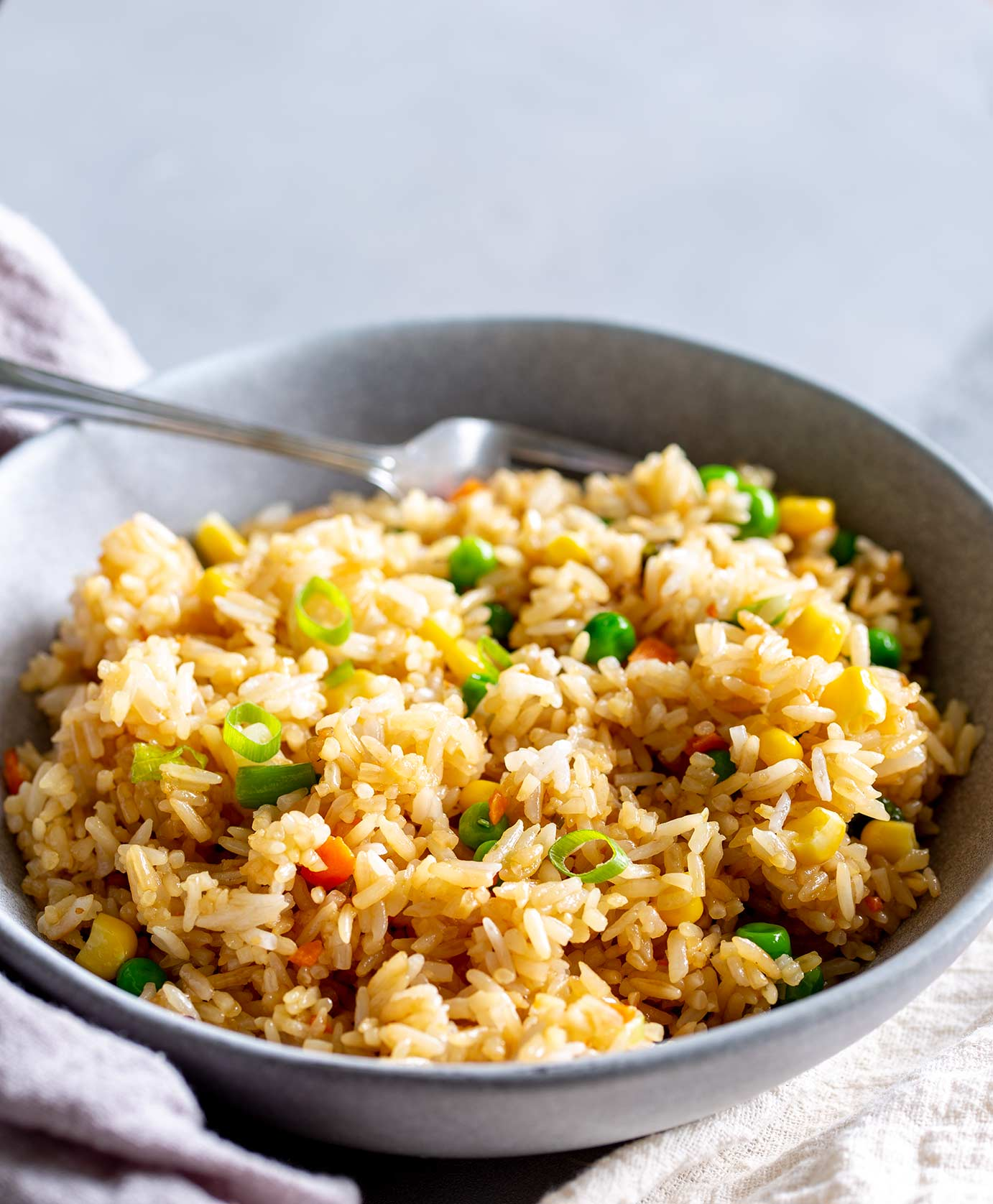 fried rice in a grey bowl with a fork at the back