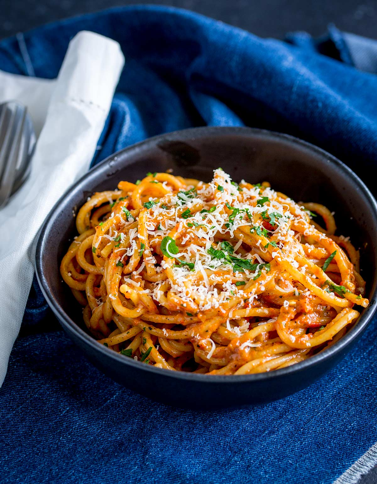spaghetti in a back bowl with a denim napkin and a silver fork