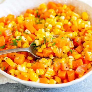 close up of a spoonful of chopped carrots and corn