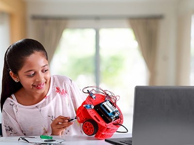 Child with Programmable Robot Kit, building and coding robots, for age 10+ years