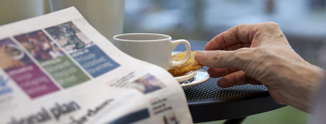 Läser tidningen och fikar