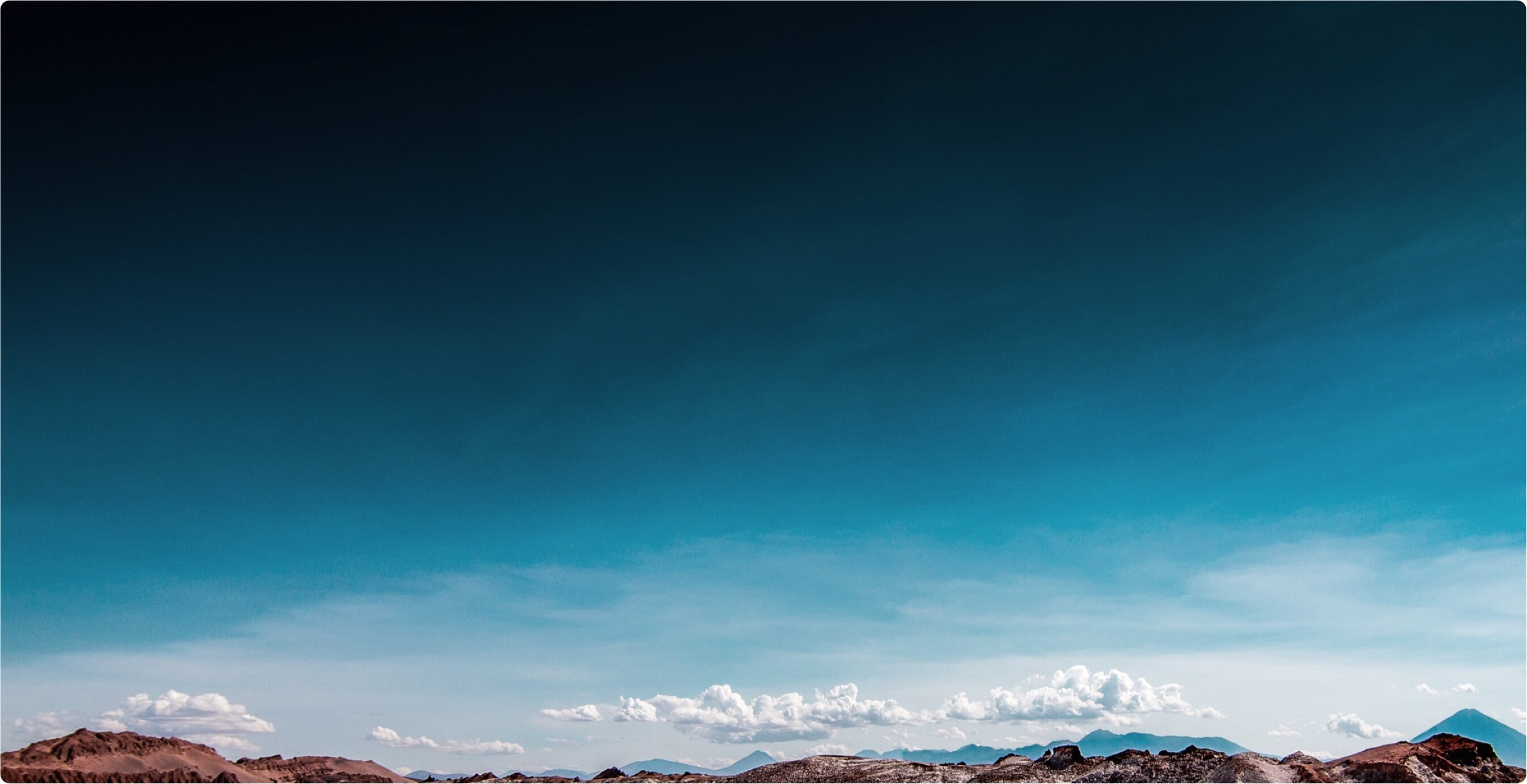 Mountain range against blue sky and clouds