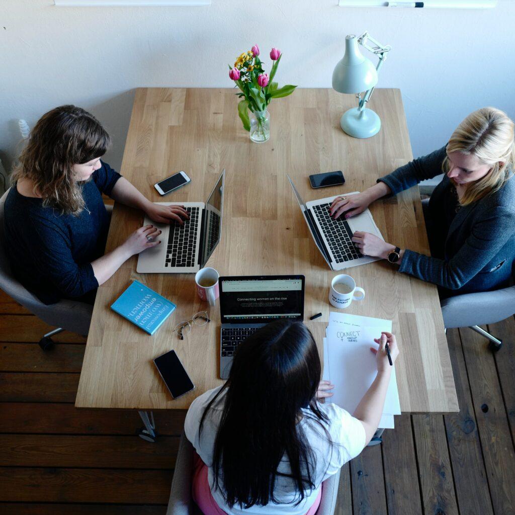 tres mujeres trabajando en sus respectivos laptops, representando a una reunión de creadores de empresa en Colombia.